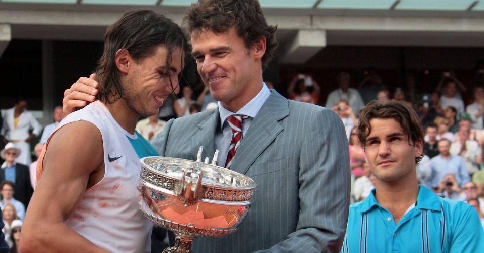 Tricampeão de Roland Garros, Gustavo Kuerten entrega o troféu ao espanhol Rafael Nadal no ano de seu terceiro título em Paris; Brasileiro lamenta até hoje por não ter podido enfrentar Nadal