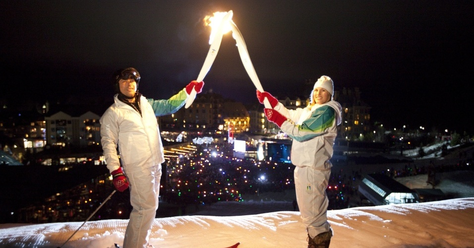 Steve Podborski, ex-atleta do esqui alpino, passa a chama olímpica a Julia Murray, ex-competidora do downhill, no revezamento da tocha em Whistler, co-sede dos Jogos