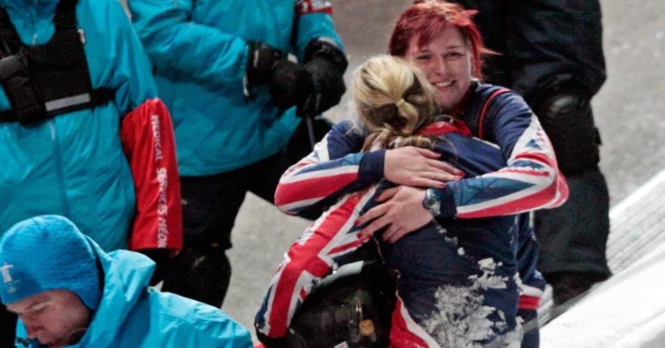 As britânicas Paula Walker e Kelly Thomas se abraçam após acidente em treino de duplas do bobsled