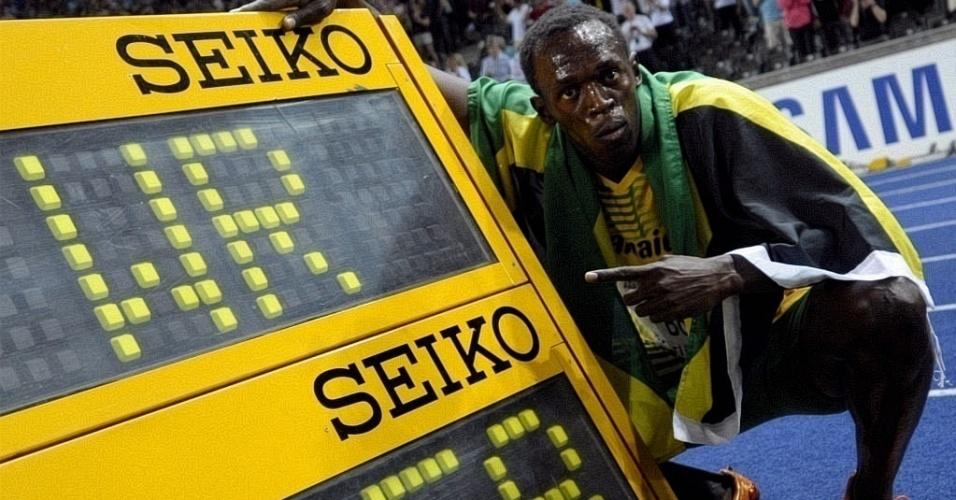 Jamaicano Usain Bolt posa ao lado do registro do recorde mundial nos 100 metros rasos em Berlim, na Alemanha