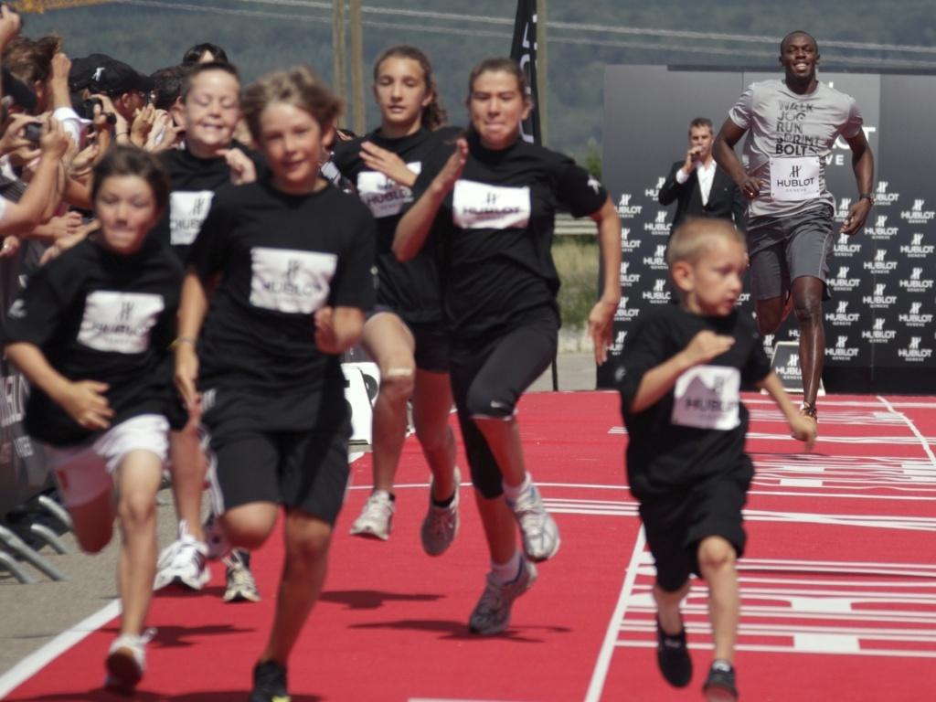 Usan Bolt corre com crianças em evento na Suíça