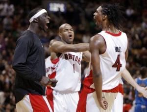 Chris Bosh (direita) comemora com companheiros a vitória dos Raptors sobre os Hornets em Toronto