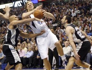 Nowitzki (c) tenta passar pela marcação de Ginóbili (d) e Jefferson, mas sobre falta na vitória do Dallas