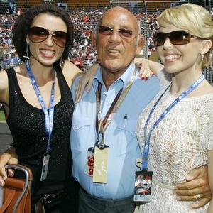Stirling Moss posa entre a cantora australiana Kylie Minogue (à direita) e sua irmã, Danni Minogue