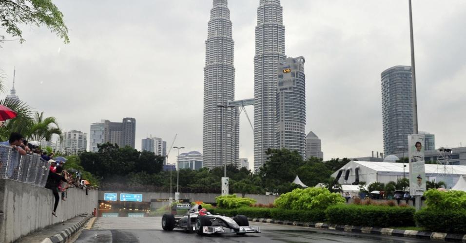 O alemão Michael Schumacher pilota carro da Mercedes em frente às Torres Gêmeas Petronas durante exibição pelas ruas de Kuala Lumpur