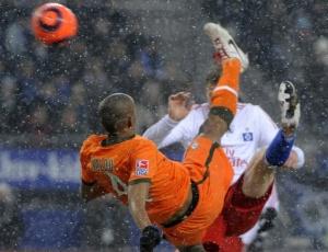 Naldo (de laranja) tenta acertar a bola na derrota do Werder Bremen para o Hamburgo no Campeonato Alemão