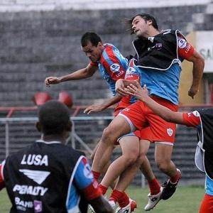 O atacante Dinei cabeceia durante treino da Portuguesa