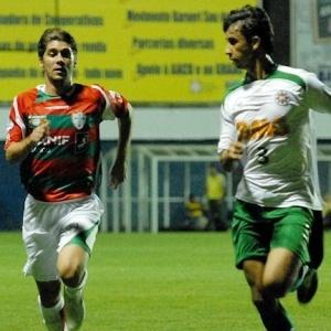 O meia Fellype Gabriel da Portuguesa tenta superar zagueiro do Ipatinga na corrida