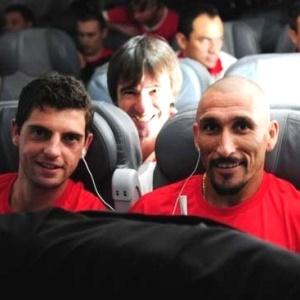 Bruno Silva e Guiñazu, em avião do Inter, observados pelo preparador físico Alejandro Valenzuela