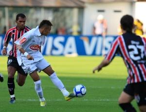 Neymar domina a bola e é cercado por marcadores do São Paulo em lance do clássico disputado na Vila Belmiro, na tarde deste domingo.