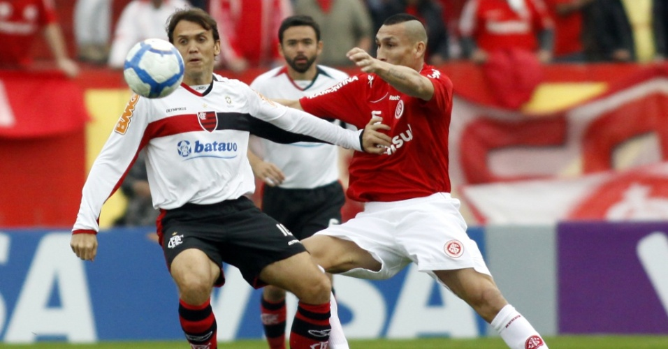 Petkovic (e) e Guiñazu disputam bola durante a partida entre Flamengo e Inter no Beira-Rio