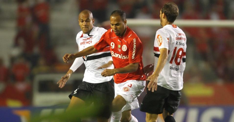Alecsandro, atacante do Inter, tenta passar pela marcação dos são-paulinos Alex Silva (e) e Rodrigo Souto (d)