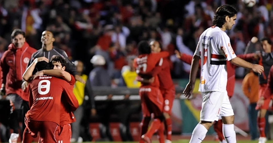 Fernandão (d) lamenta a eliminação do São Paulo, enquanto os jogadores do Inter comemoram a classificação à final da Libertadores