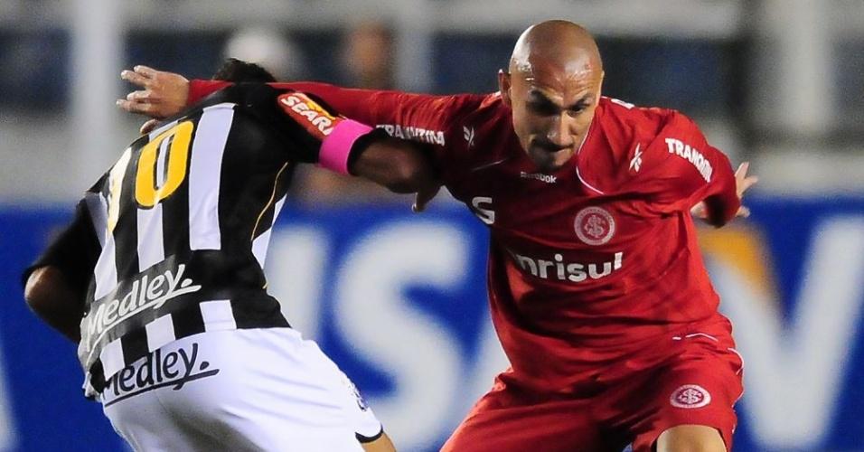 Guiñazu desarma jogador do Santos na partida desta quarta-feira, na Vila Belmiro